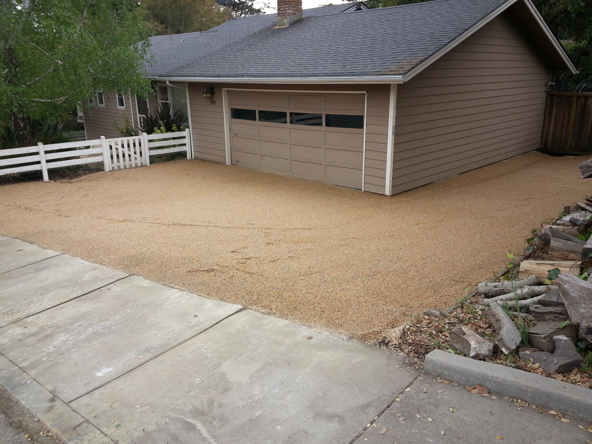 Gold gravel and a layer of base rock underneath allow rainwater to infiltrate